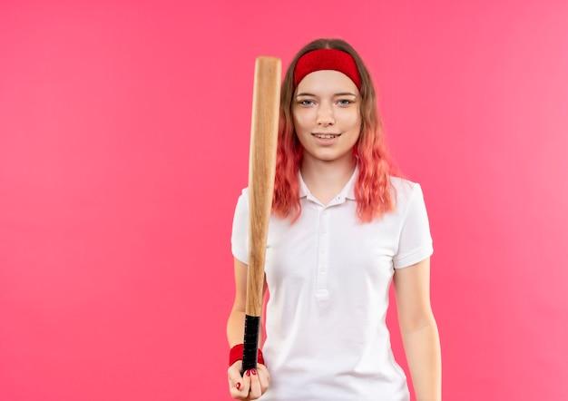 Jonge sportieve vrouw in hoofdband die honkbal gaat spelen met een knuppel, die zelfverzekerd glimlachend over roze muur kijkt