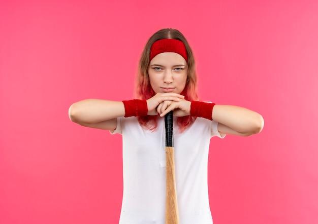 Jonge sportieve vrouw in hoofdband die honkbal gaat spelen met een knuppel, met zelfverzekerde uitdrukking die zich over roze muur bevindt