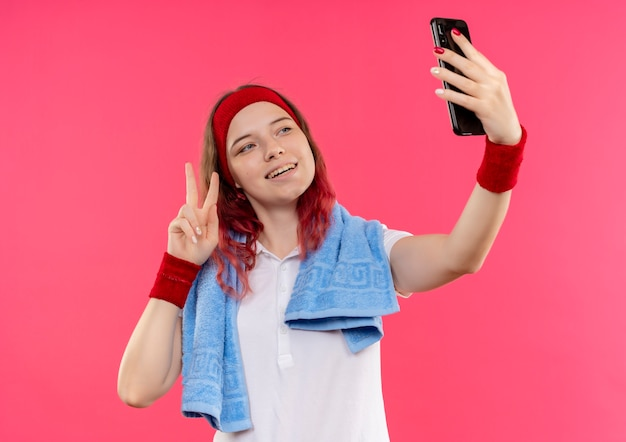 Jonge sportieve vrouw in hoofdband met handdoek op schouder die een selfie van zichzelf neemt die overwinningsteken toont aan camera van haar smartphone die zich over roze muur bevindt