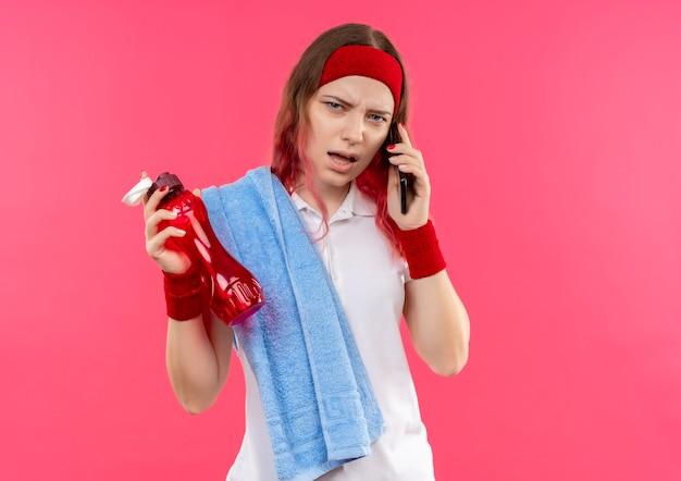 Jonge sportieve vrouw in hoofdband met handdoek op schouder die fles water vasthoudt terwijl ze aan een telefoon spreekt en kijkt verward en erg angstig over roze muur
