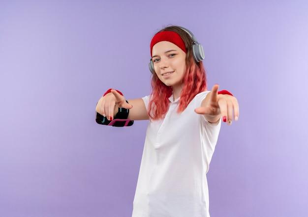 Jonge sportieve vrouw in hoofdband met koptelefoon glimlachend wijzend met vingers naar camera, training met smartphone armband staande over paarse muur