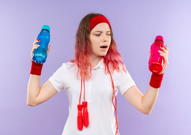 Jonge sportieve vrouw in hoofdband met springtouw om haar nek die twee flessen water vasthoudt en verward kijkt terwijl ze probeert een keuze te maken die over de paarse muur staat