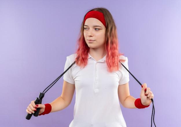 Jonge sportieve vrouw in hoofdband met springtouw opzij kijken met zelfverzekerde glimlach op gezicht staande over paarse muur
