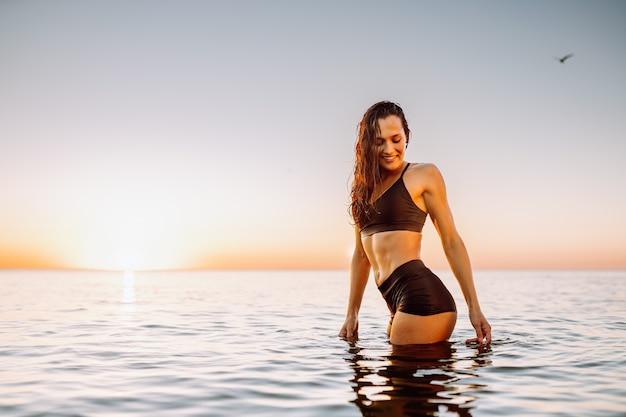 Jonge sportieve vrouw in kalme zee bij zonsondergang in zwarte sportkleding. ruimte voor bericht.
