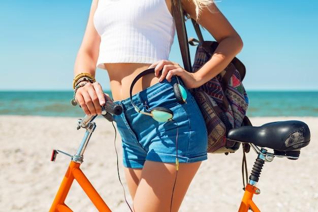 Jonge sportieve vrouw in stijlvolle witte crop top en denim shorts staande op het strand met oranje fiets