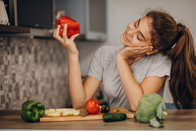 Jonge sportieve vrouw koken in de keuken