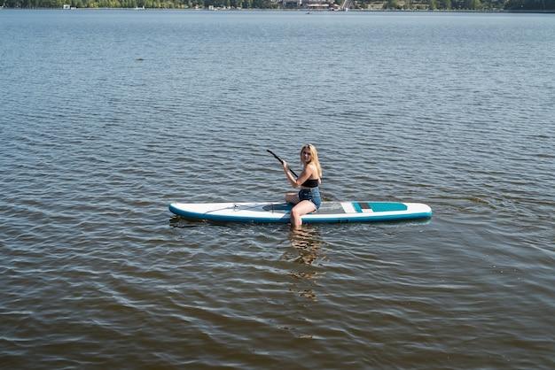 Jonge sportieve vrouw liggend en ontspannen op sup board blauwe vijverwater. zomervakantie