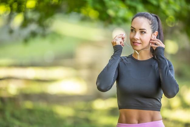 Jonge sportieve vrouw loper met een mooie glimlach voor het hardlopen met koptelefoon luistert naar motiverende muziek.