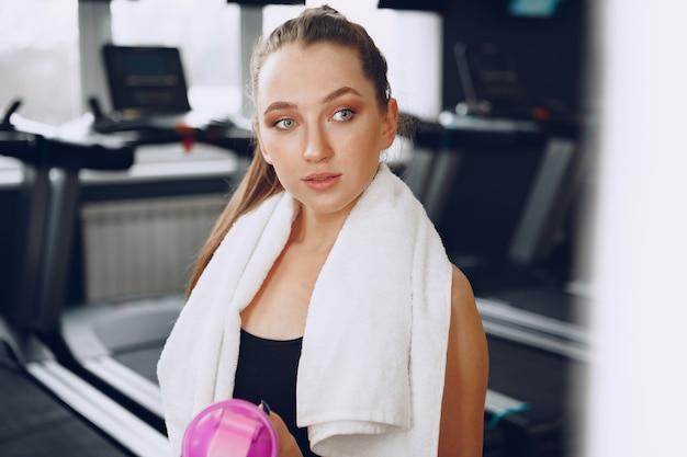 Jonge sportieve vrouw met een drankje in een sportschool na training