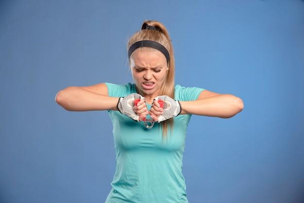 Jonge sportieve vrouw met een hand die tandvlees uitrekt en probeert het uit te rekken.