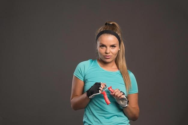 Jonge sportieve vrouw met een hand die zich uitrekt gom