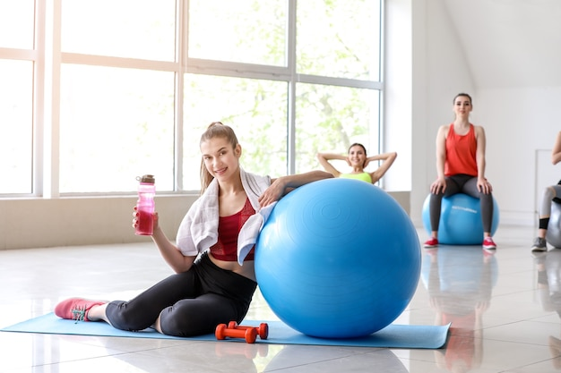 Jonge sportieve vrouw met fitball drinkwater in sportschool in