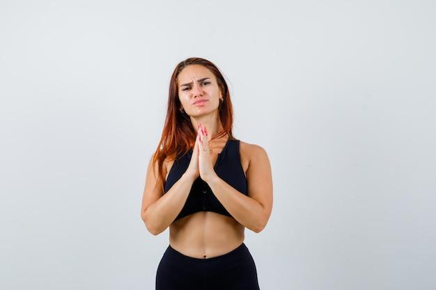 Jonge sportieve vrouw met lang haar bidden