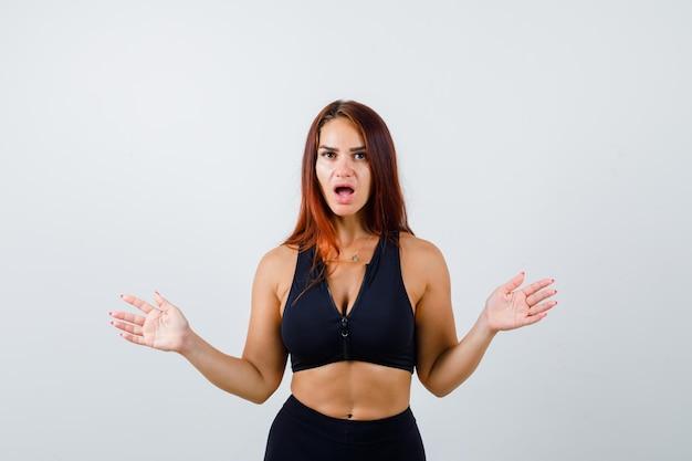 Jonge sportieve vrouw met lang haar die geschokt is