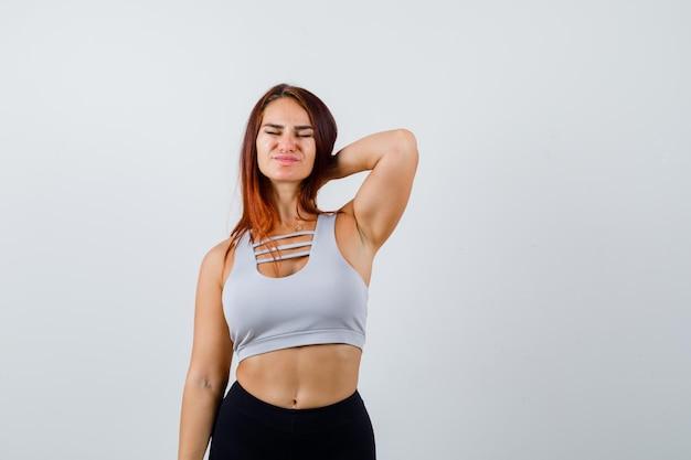 Jonge sportieve vrouw met lang haar in een grijze top