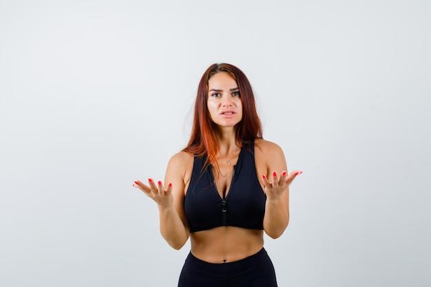 Jonge sportieve vrouw met lang haar in een zwarte top