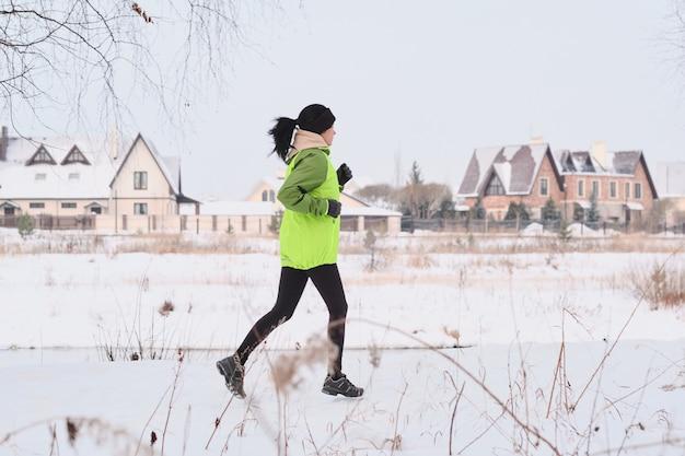 Jonge sportieve vrouw met paardenstaart die dicht bij plattelandshuizen loopt tijdens het trainen in de winter