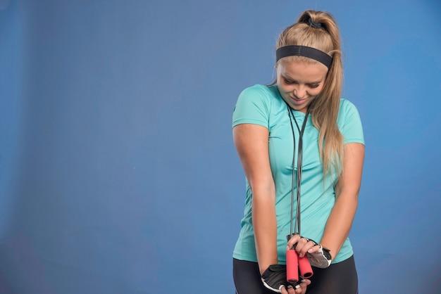 Jonge sportieve vrouw met springtouwen onder haar kin.