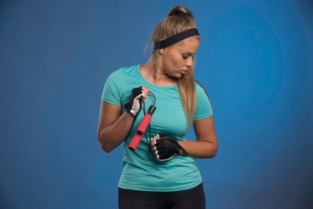 Jonge sportieve vrouw met touwtjespringen en opzij kijken.