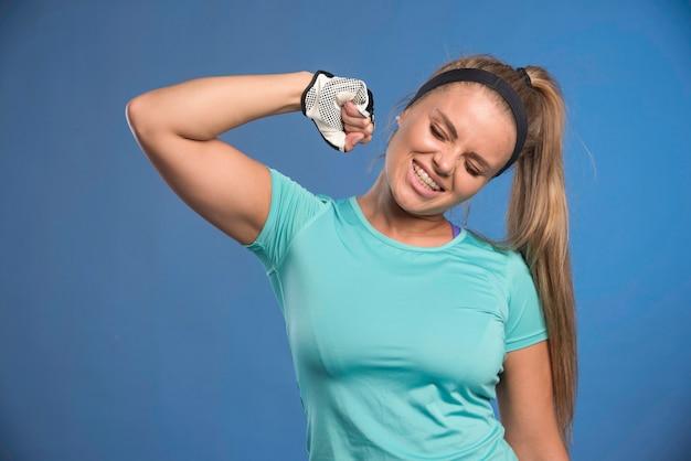 Jonge sportieve vrouw met vuisten en haar spier aantonen.