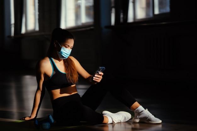 Jonge sportieve vrouw na het beoefenen van yoga met smartphone