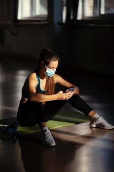 Jonge sportieve vrouw na het beoefenen van yoga, pauze in het doen van oefening, ontspannen op yogamat