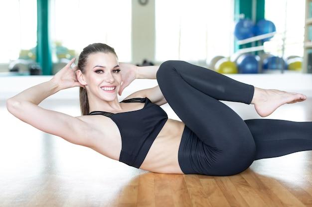 Jonge sportieve vrouw oefenen, kriskras oefenen, fiets crunches vormen, trainen, sportkleding dragen, zwarte broek en top, volledige lengte binnen.