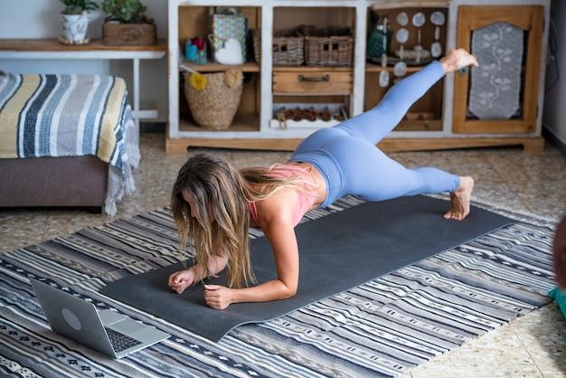 Jonge sportieve vrouw thuis trainen tiener doen fitness oefeningen op de vloer van de woonkamer voor het vormgeven van het lichaam van de billen met behulp van online persoonlijk trainingsprogramma met laptop doen push ups pilates