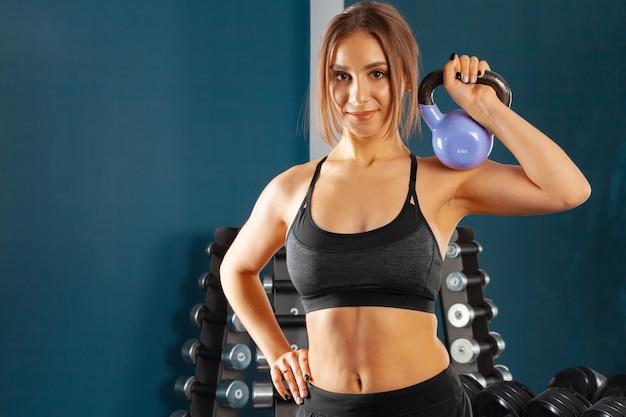 Jonge sportieve vrouw training met halters. sport en bodybuilding concept