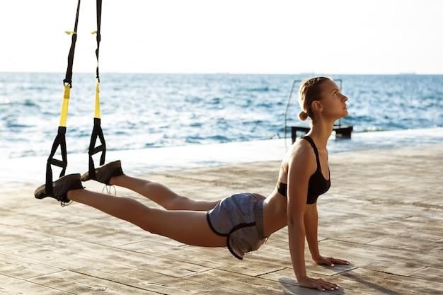 Jonge sportieve vrouw training met trx in de buurt van de zee in de ochtend