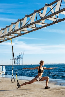 Jonge sportieve vrouw training met trx in de buurt van de zee in de ochtend.