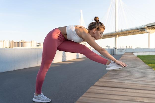 Jonge sportieve vrouw warming-up en been strekken voor ochtendrun met brug op achtergrond
