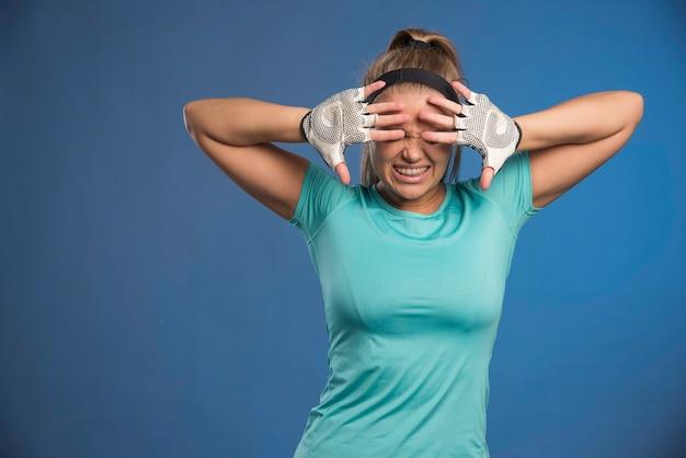 Jonge sportieve vrouw ziet er moe uit en sluit haar ogen.