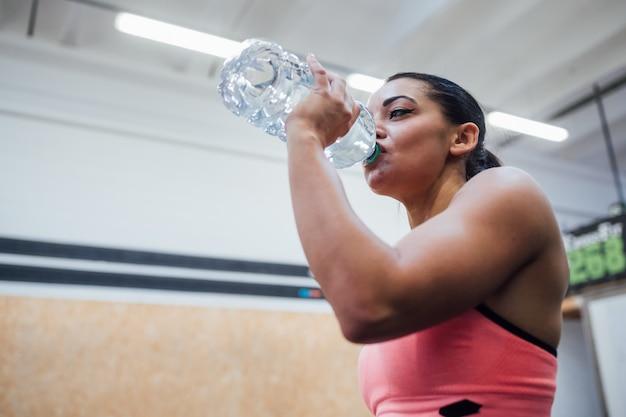 Jonge sportieve vrouwen binnengymnastiek die drinkwater terugkrijgt