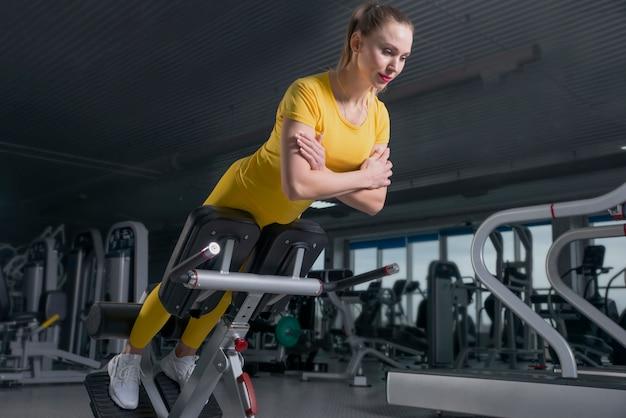Jonge sportieve vrouwentraining op oefeningenmachine in gymnastiek