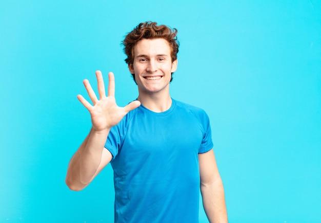 Jonge sportjongen die lacht en er vriendelijk uitziet, nummer vijf of vijfde toont met de hand naar voren, aftellend