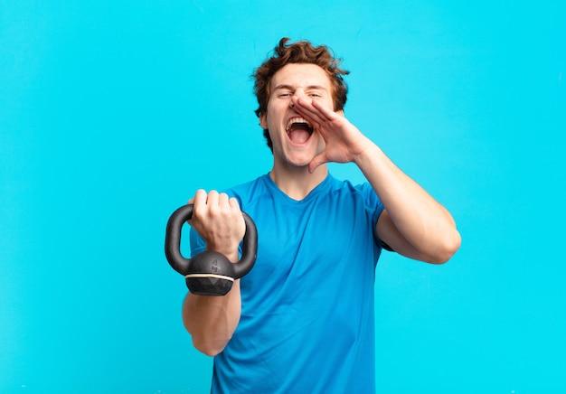 Jonge sportjongen die zich gelukkig, opgewonden en positief voelt, een grote schreeuw geeft met de handen naast de mond, roept halter concept