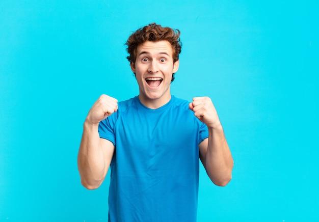 Jonge sportjongen die zich geschokt, opgewonden en gelukkig voelt, lacht en succes viert, en zegt wow!