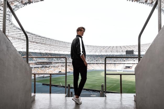 Jonge sportman bij groot leeg voetbalstadion kijken vanaf de top. hij kijkt terug naar de camera