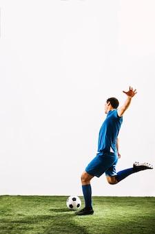 Jonge sportman die bal met macht schopt