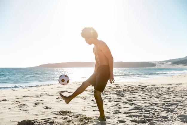 Jonge sportman die bal op zeekust werpt