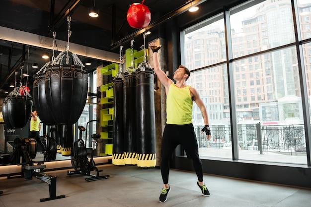Jonge sportman die gewichtsbal werpen bij de gymnastiek