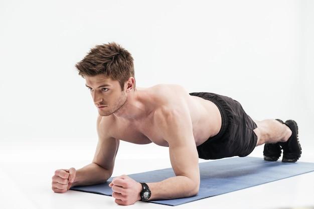 Jonge sportman die plankoefening op een geschiktheidsmat doet