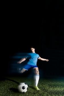 Jonge sportman die voetbalbal schoppen