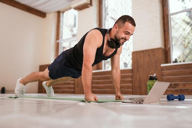 Jonge sportman doet push-ups oefenen in een lege sportschool of thuis kijken naar online sportvideo's