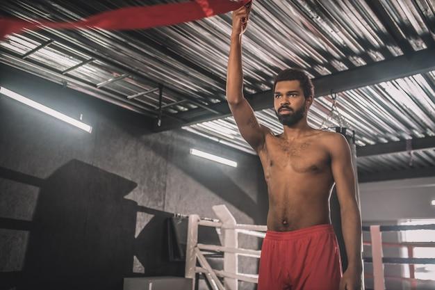 Jonge sportman. donkere jonge sportman in een sportschool die zich klaarmaakt voor de training
