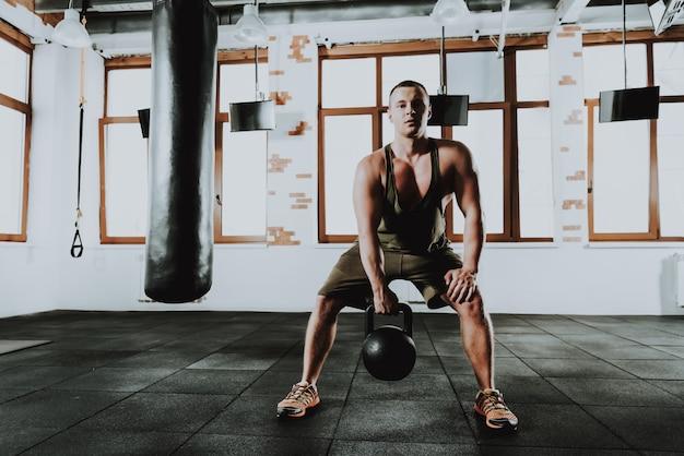 Jonge sportman is aan het trainen in de sportschool met vrouwen