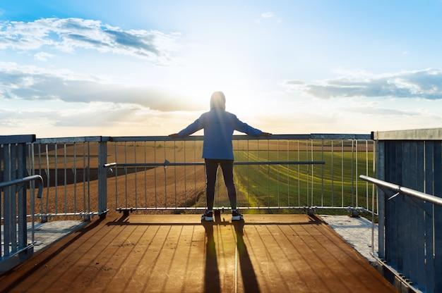 Jonge sportman kijkt naar de landbouwvelden over de leuning van de brug. dramatische avondscène, stralen van de ondergaande zon.