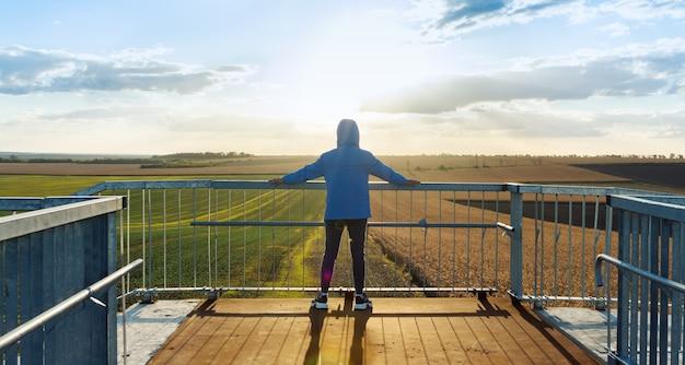 Jonge sportman kijkt naar de landbouwvelden terwijl hij op de brug staat en op de reling leunt. avondtijd, stralen van de ondergaande zon, schittering.
