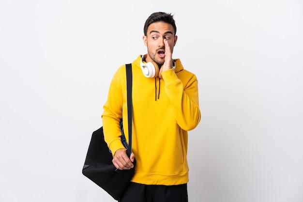Jonge sportman met sporttas die op witte muur wordt geïsoleerd die iets met verrassingsgebaar fluistert terwijl hij naar de zijkant kijkt